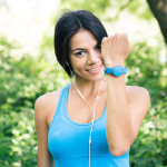 Smiling sporty woman in headphones showing activity tracker on hand outdoors in park