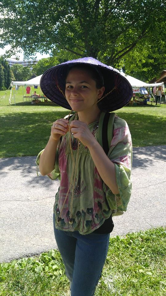 Customer trys on Asian Hat at the Common Ground Festival