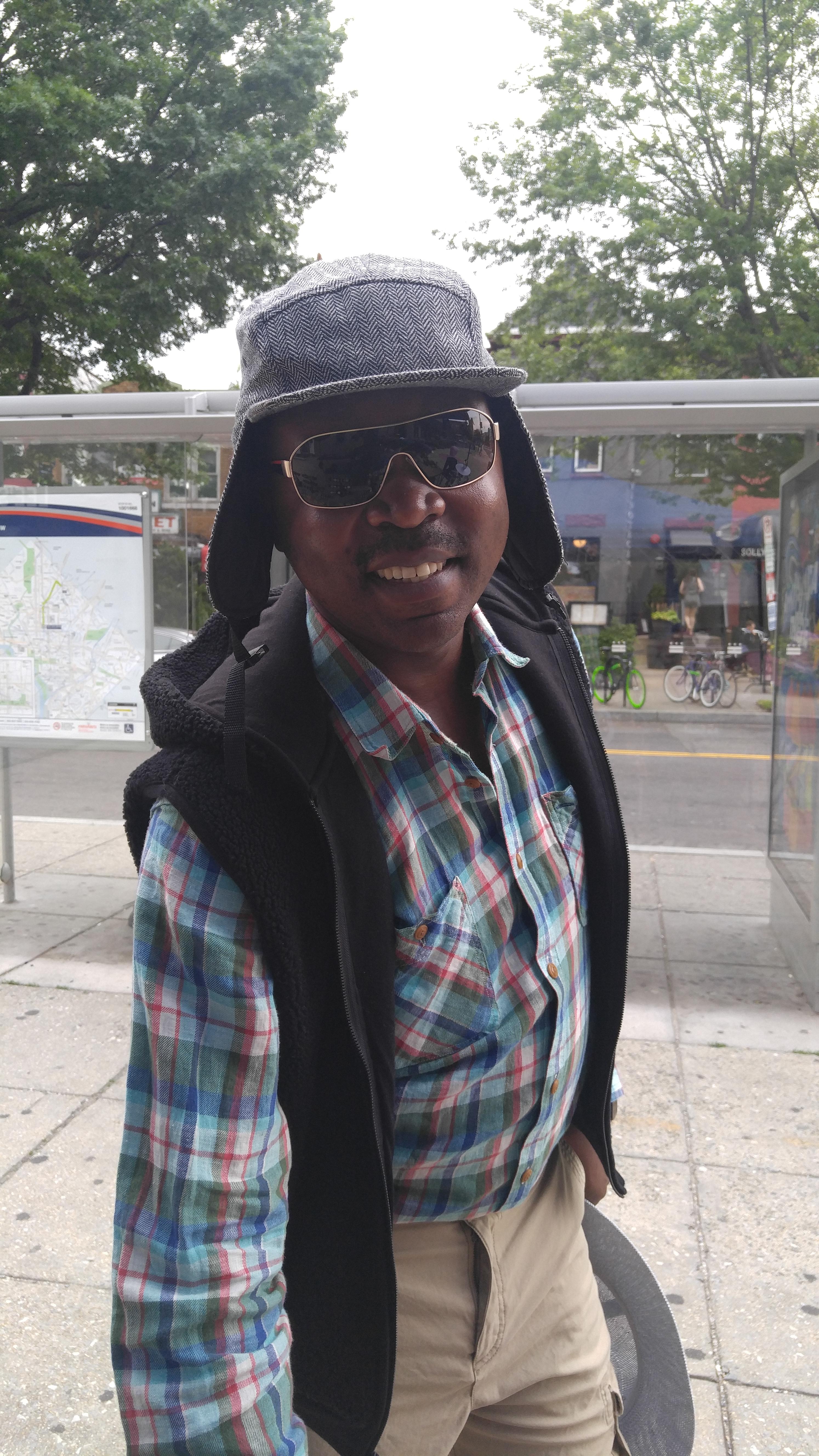 Customer in earflap tweed cap & sport sunglasses